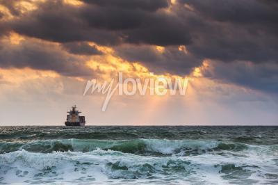 Fototapeta Sun setting at the sea with sailing cargo ship